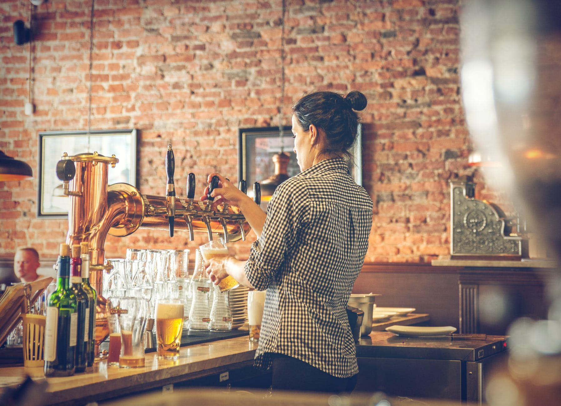 photo of bartender pouring draught beer